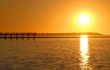See scenic landmarks such as the Urangan Pier on the Champagne Sunset Sail cruise aboard luxury yacht Blue Dolphin.
